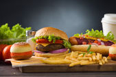 Burger with fast food items and materials on the background — Stock Photo