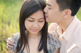 Chinese romantic couple kissing forehead in a park — Stock Photo