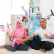 Malaysian family celebrating while watching television over a to — Stock Photo #26599567