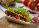 Hot dog and bacon served with mustard tomatoes and plenty of bac — Stock Photo