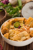 Curry noodle malaysian penang style with raw ingredients on back — Stock Photo