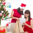 Stock Photo: Chinese girls online shopping during christmas celebration