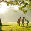 Stock Photo: An asian family having fun playing in the park early morning