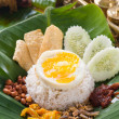 Nasi lemak, a traditional malay curry paste rice dish served on  — Stock fotografie