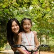 Stock Photo: Asichinese mother teaching her daughter riding bicycle outdoo