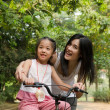 Asian chinese mother teaching her daughter riding bicycle outdoo — Stock Photo