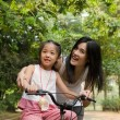 Asian chinese mother teaching her daughter riding bicycle outdoo — Stock Photo #27242537