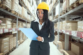 Indian woman doing stock tick on warehouse — Stock Photo