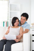 Asian couple. Husband and 8 months pregnant wife using tablet co — Stock Photo