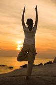 Female yoga silhouette on beautiful beach during sunset — Stock Photo