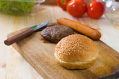 Hamburger fast food ingredients with plenty of raw materials on — Stock Photo
