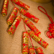 Traditional chinese new year fire crackers on the red. — Stock Photo #28965669