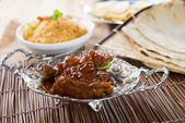 Butter chicken curry with basmati rice and various indian foods — Stock Photo