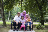 Malay family sitting and having fun in the park — Stock Photo