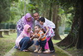 Malay muslim family having fun playing in the park — Stock Photo
