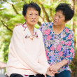 Crying Asian senior mother with her senior daughter at outdoor p — Stock Photo