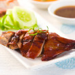 Chinese roast duck drumstick served with chili and cucumbers — Stock Photo