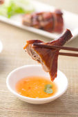 Chopstick holding chinese roast duck served with soya sauce and — Stock Photo