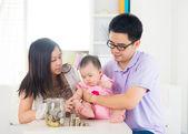 Asyalı bebek pare yardımı ile cam şişe içine para koyarak — Stok fotoğraf