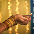 Stock Photo: Diwali festival of lights , hands holding indian oil lamp