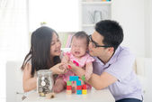 Crying asian baby being comforted by chinese parents — Stock Photo