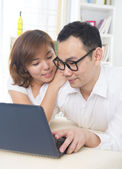 Young Asian couple using tablet — Stock Photo