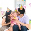 Asian chinese parent kissing baby on birthday party — Стоковое фото
