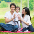 Asian father and pregnant wife and daughter enjoying outdoor pin — Stock Photo