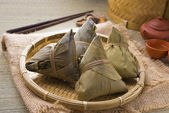 Rice dumplings and chinese tea on bamboo place mat — Stock Photo