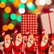 Stock Photo: Toy santa claus with christmas gifts on the background
