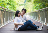 Happy young pregnant asian couple in the nature — Stockfoto