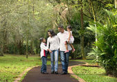 Happy indian family walking outdoor in the park — Stock Photo