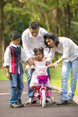 Indian family guiding little daughter to cycle — Stock Photo