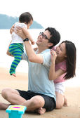 Family playing on the beach — Stock Photo