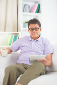 Senior asian chinese enjoying on a sofa — Stockfoto