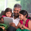 Father with his daughters using a tablet computer — Stock Photo #48123615
