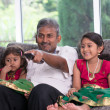 Indian father watching tv with his daughters — Stock Photo