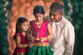 Fagther and daughters celebrating diwali — Stock Photo