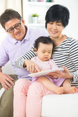 Asian grandparents teaching granddaughter internet — Stockfoto
