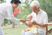 Asian grandparents playing with grandson — Stock Photo