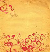 Yellow old paper background with red hearts and flourishes — Stock Photo