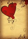 Red heart on yellow old paper — Stock Photo