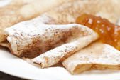 Close up of crepes with powdered sugar and jam — Stock Photo