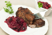Eating juicy steak with plum relish — Stock Photo