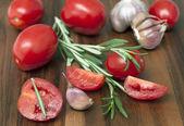 Fresh tomatoes, rosemary and garlic. Selected focus — Stock Photo