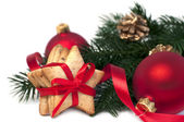 Two red christmas balls with gold ribbon and cookies, isolated on white, selective focus — Stockfoto