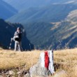 Young man walking on a marked path in the mountains - Stock Photo