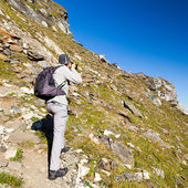 Young tourist taking photos outdoor in the mountain landscape — Stock Photo