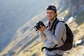 Portrait of a tourist taking photos outdoor in the mountain land — Stock Photo