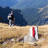 Young man walking on a marked path in the mountains — Stock Photo